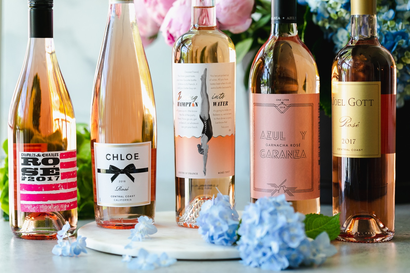 Shot of bottles of rosé with flowers in the background