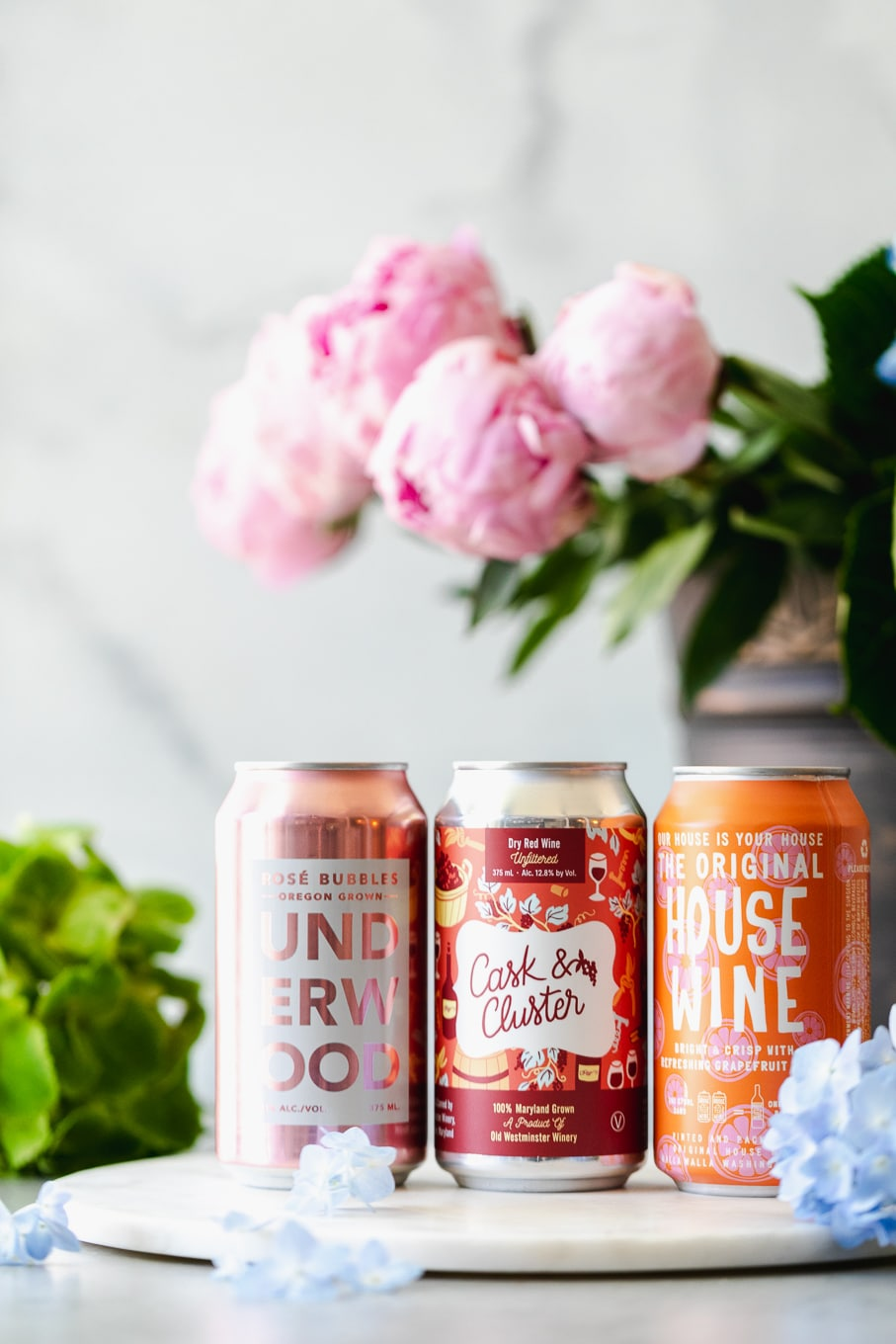 Shot of 3 canned wines with flowers in the background