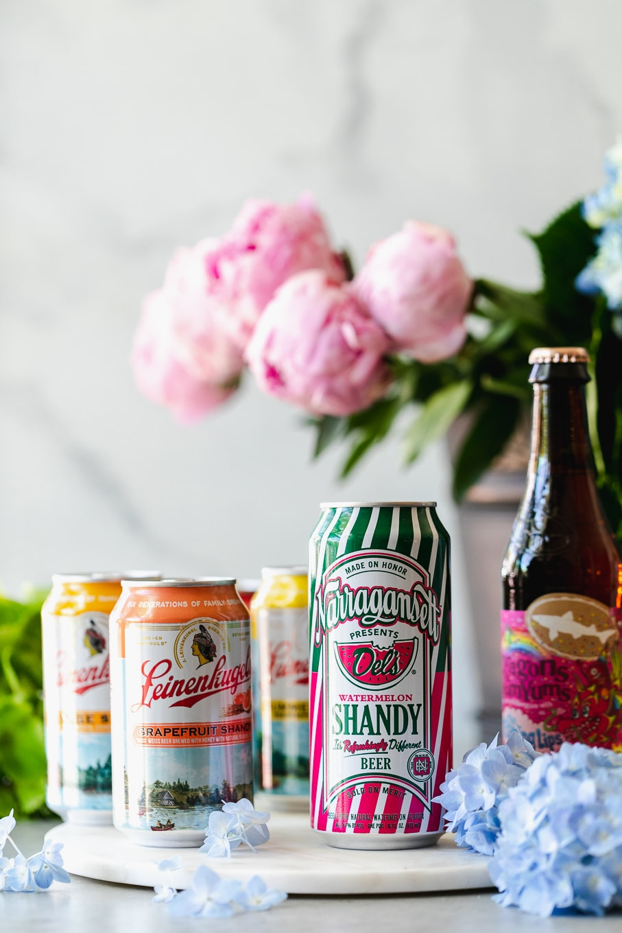 Shot of colorful labeled beers with flowers in the background