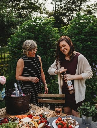 Shot of two women smiling and opening a bottle of wine