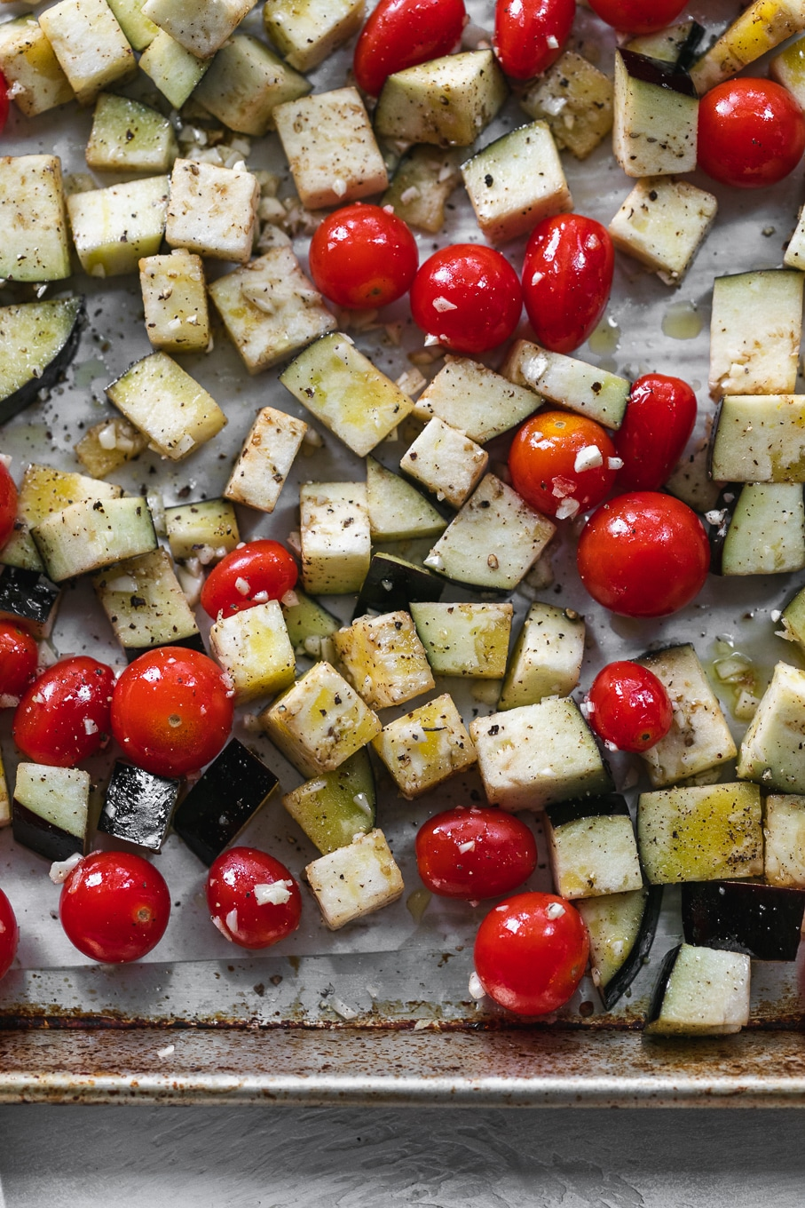 Overhead close up shot of a sheet pan filled with tomatoes and eggplant