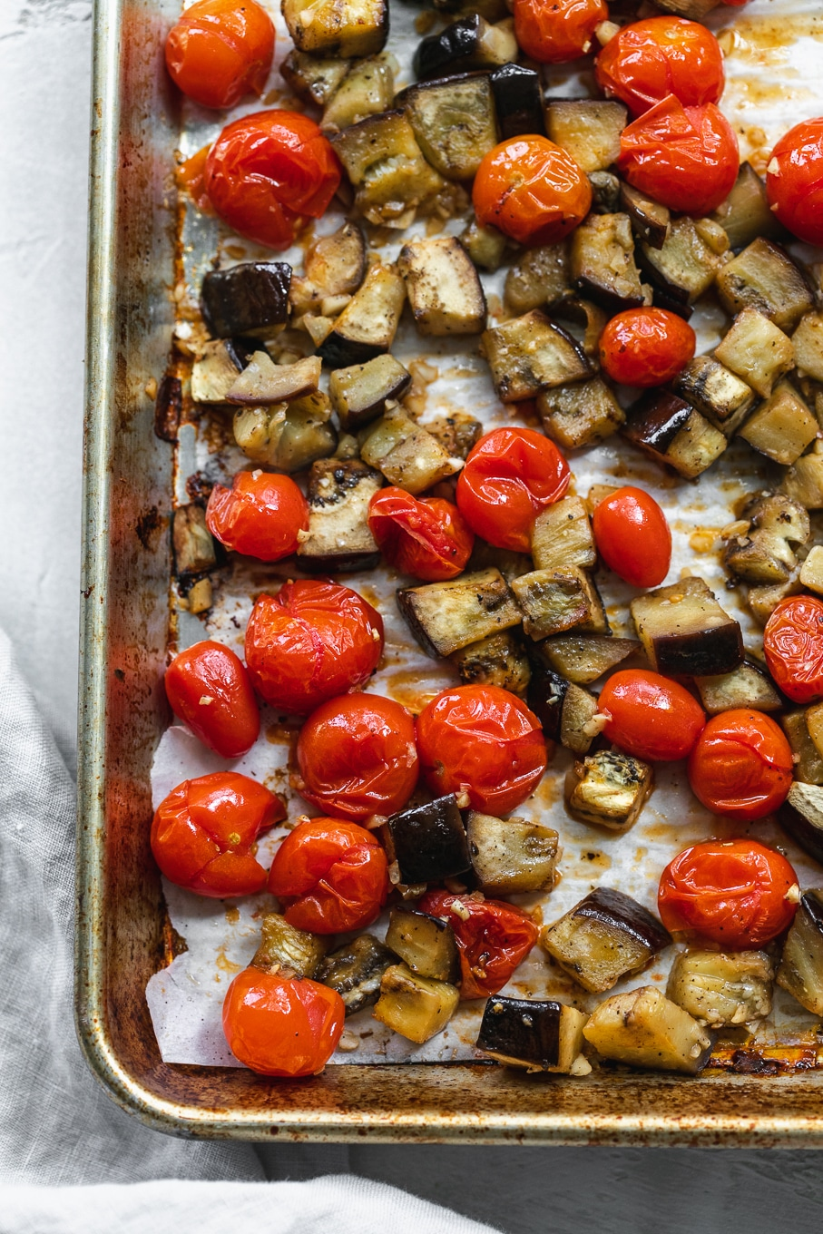 Overhead close up shot of a sheet pan filled with roasted tomatoes and eggplant