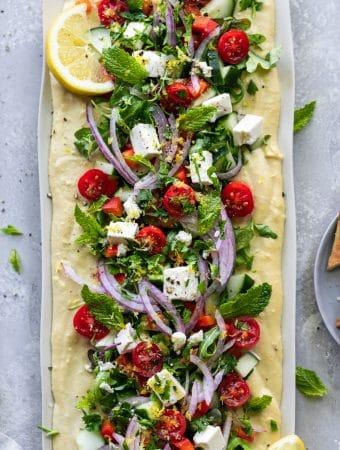 Overhead shot of greek salad hummus board with feta, tomatoes, and herbs