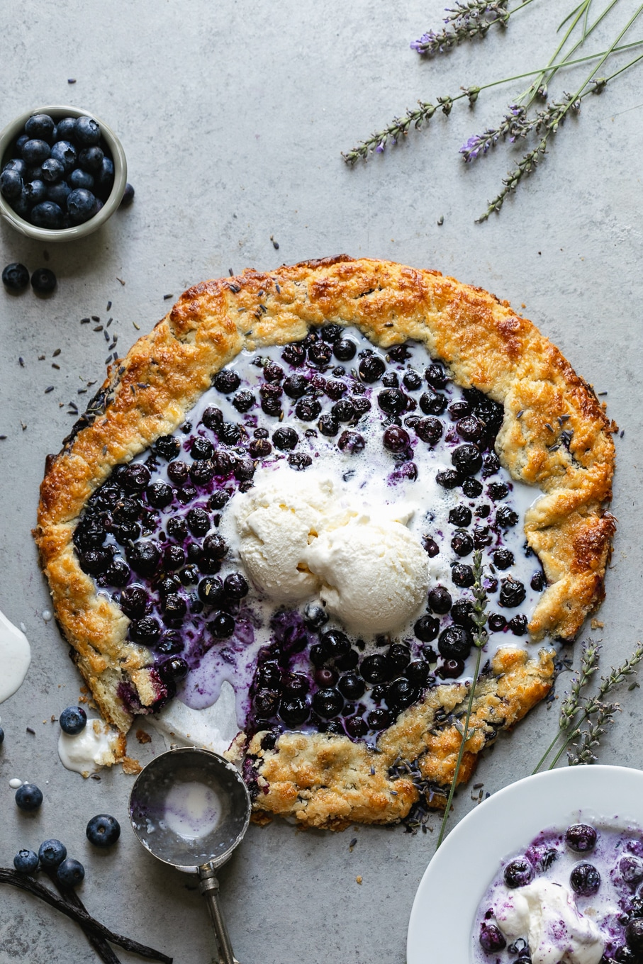 Overhead shot of a blueberry galette with melting vanilla ice cream on top