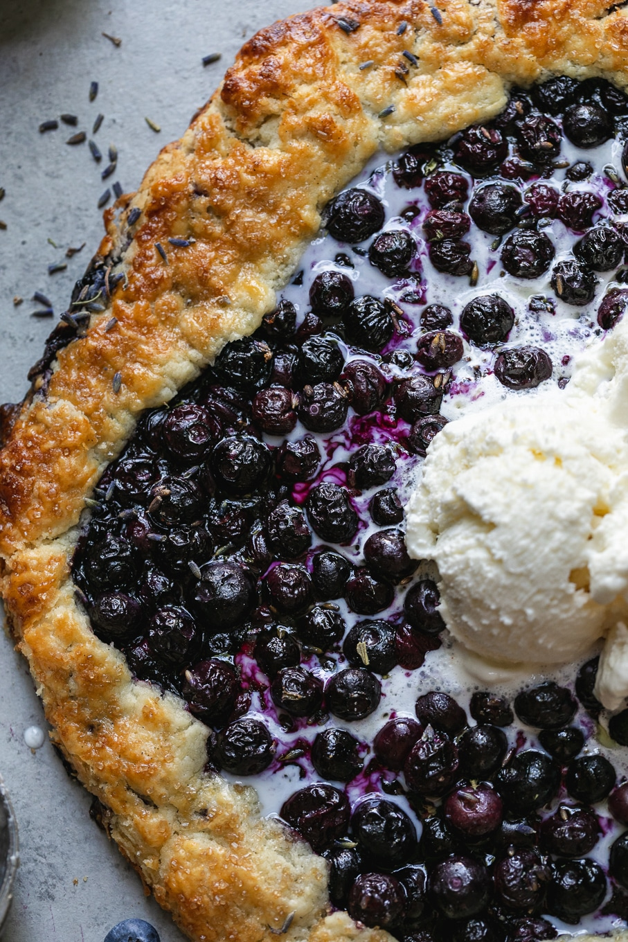 Overhead close up shot of a blueberry galette with melting vanilla ice cream on top