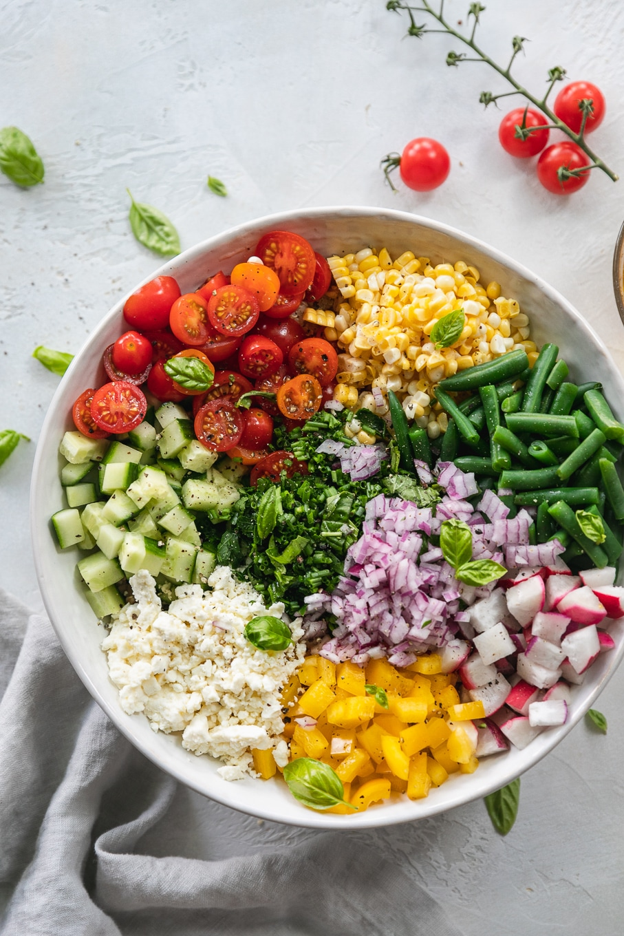 Overhead shot of a bowl of feta, bell pepper, red onion, radishes, green beans, corn, tomatoes, and cucumber