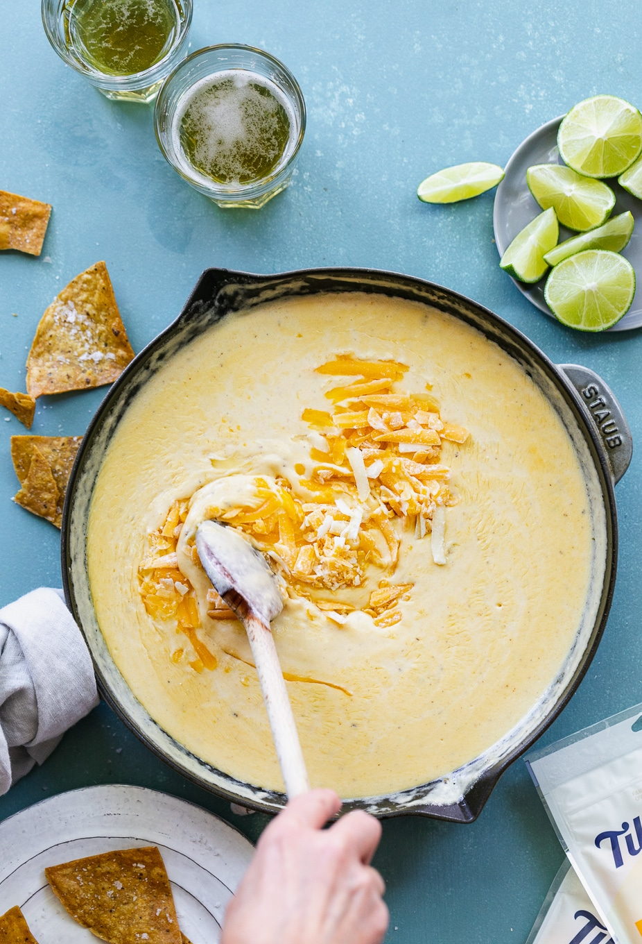 Overhead shot of a skillet of beer cheese dip with cheese being stirred into it