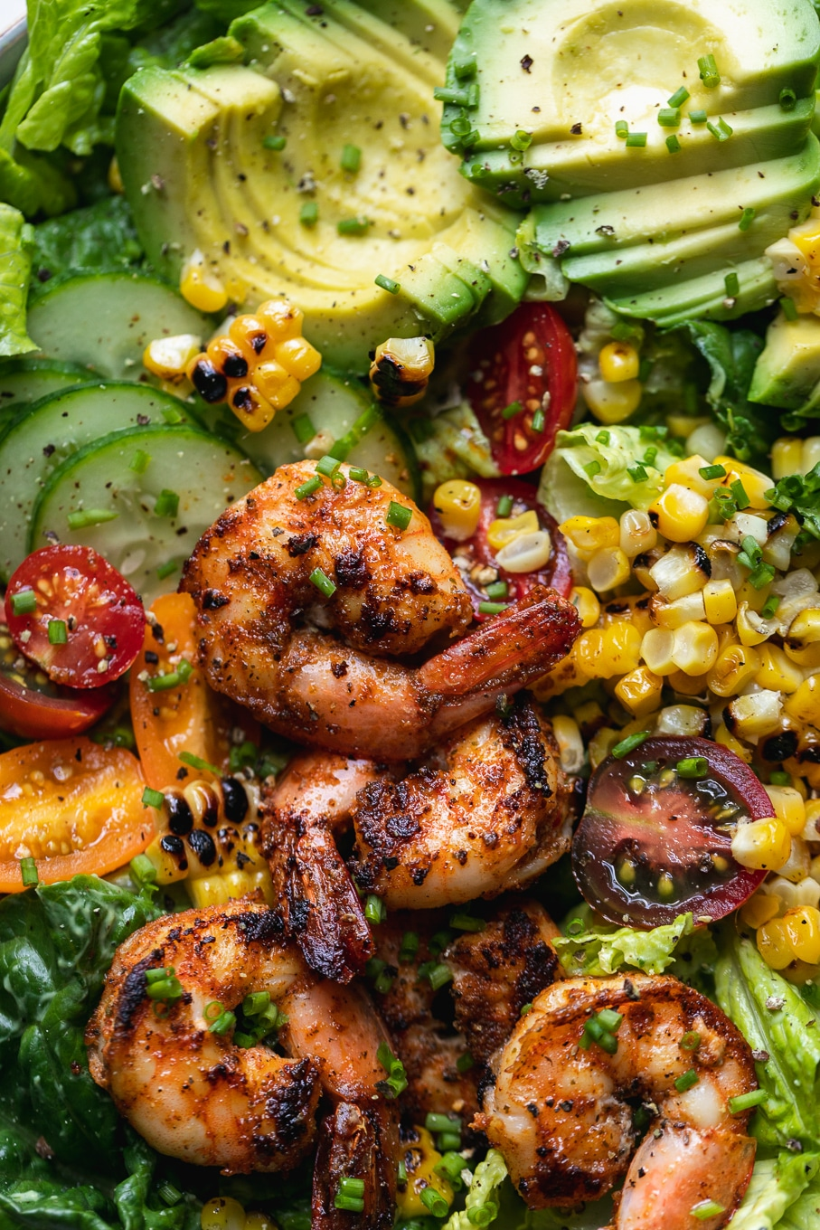 Super close up shot of shrimp, tomatoes, corn, avocado, and cucumbers