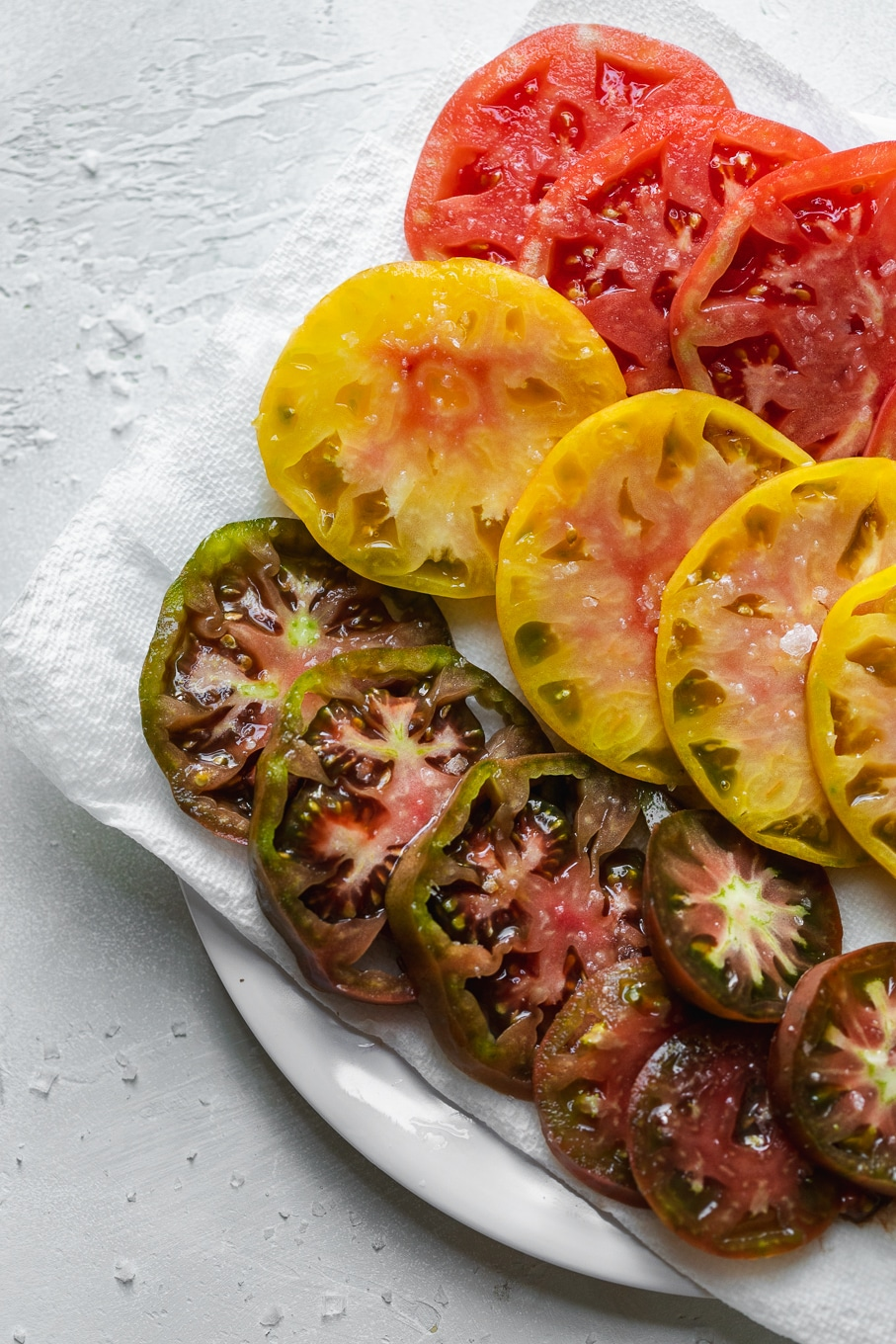 Overhead shot of a plate with sliced heirloom tomatoes on it