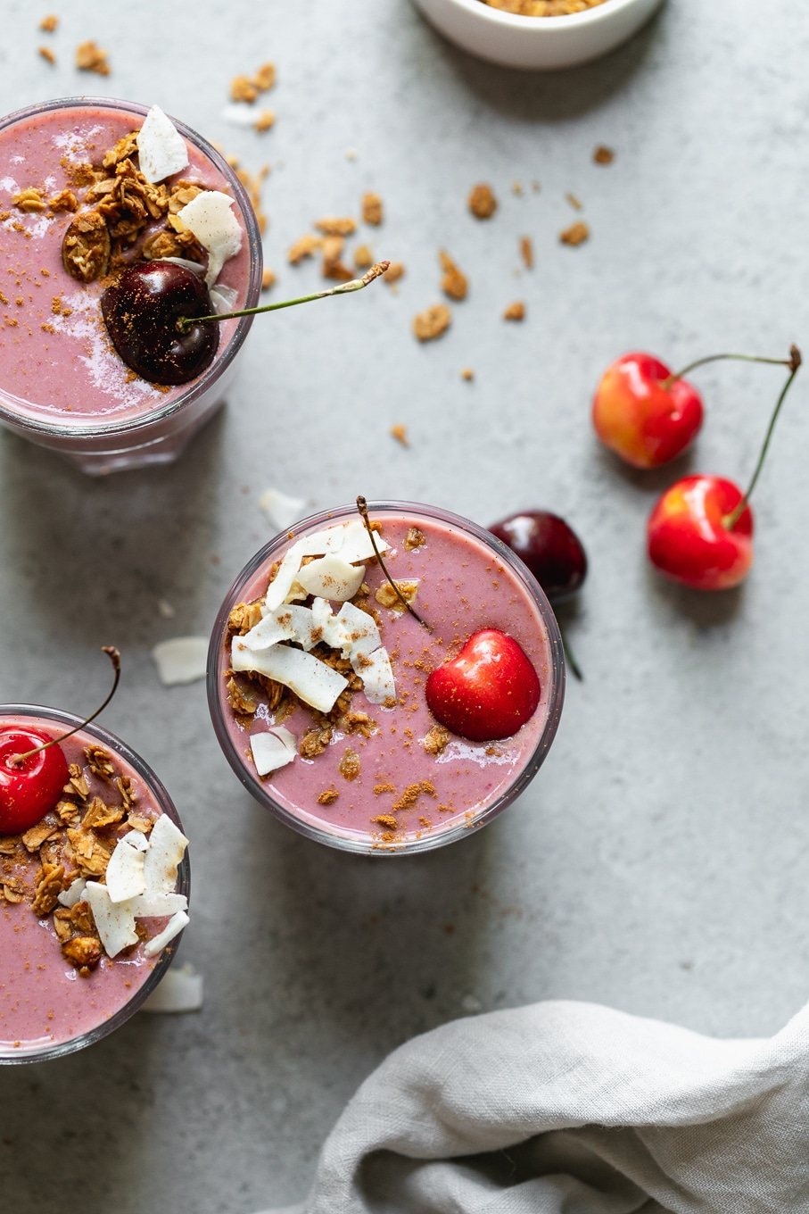 Overhead shot of 3 cherry smoothies topped with coconut and granola