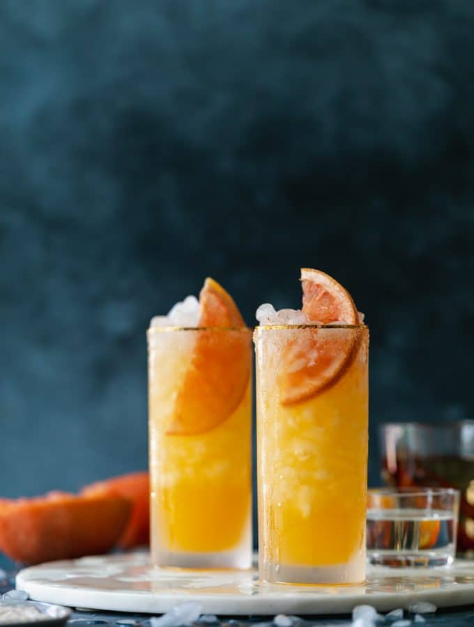 Straight on shot of grapefruit cocktails against a dark blue background