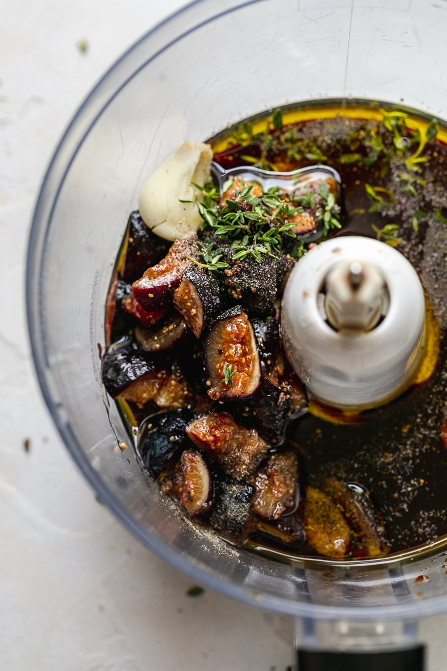 Overhead shot of a food processor filled with roasted figs, balsamic, olive oil, and herbs