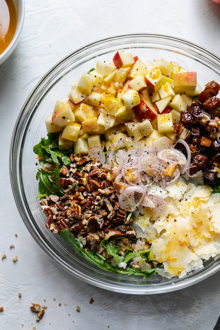 Close up shot of a bowl filled with arugula and piles of pecans, parmesan, apples, and dates