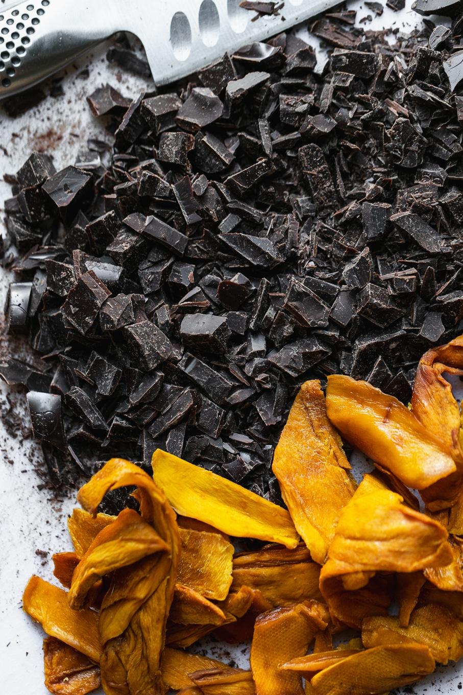Overhead close up shot of chopped dark chocolate and dried mango