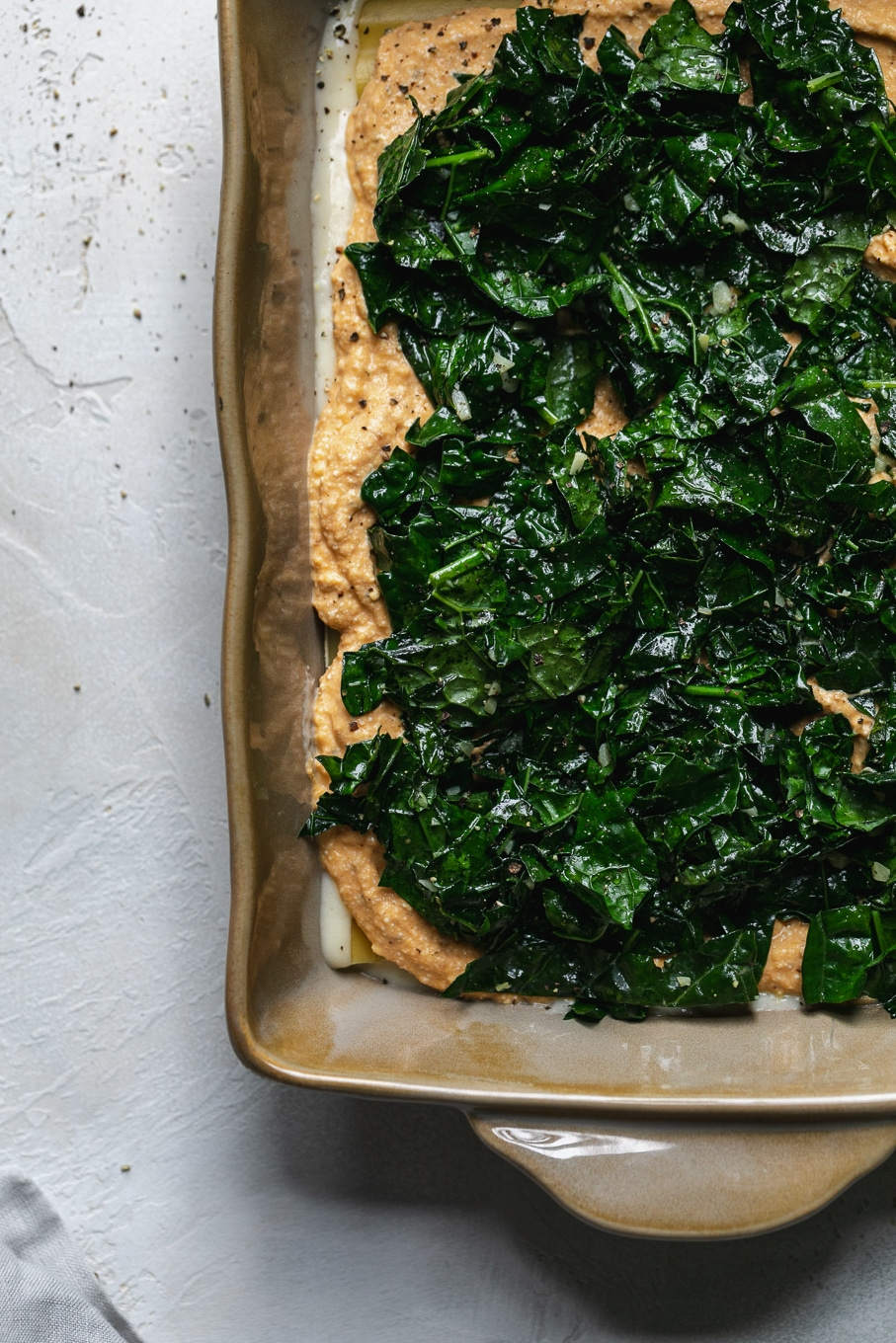 Overhead shot of lasagna being layered with kale