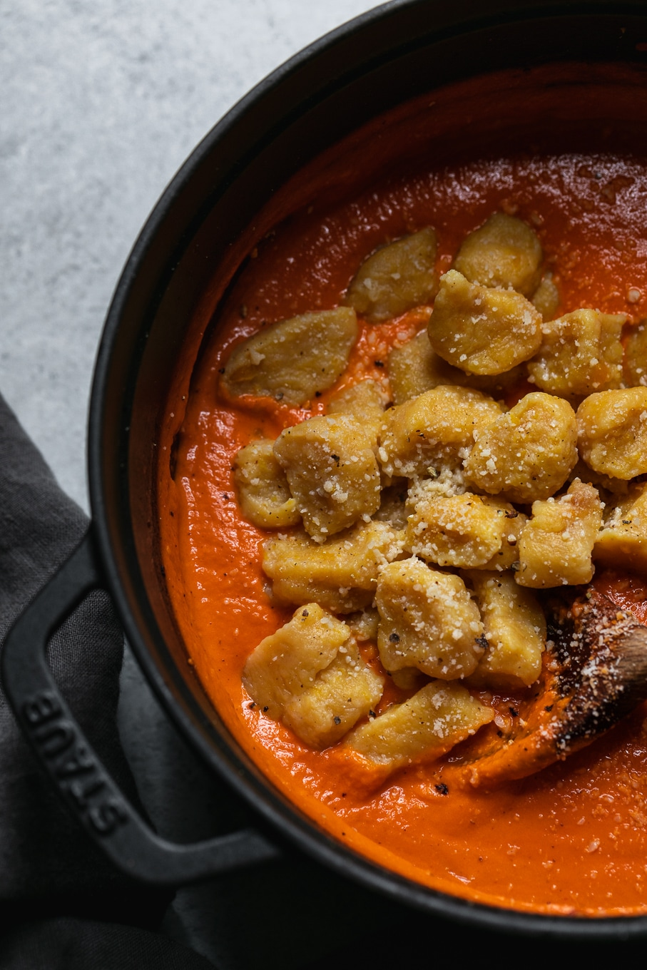 Overhead close up shot of a black dutch oven filled with vodka sauce and gnocchi about to be stirred with a wooden spoon