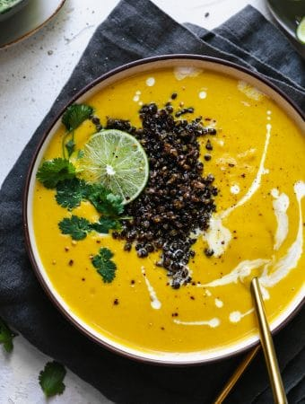 Overhead shot of a bowl of golden cauliflower soup with lentils, lime, and cilantro on top