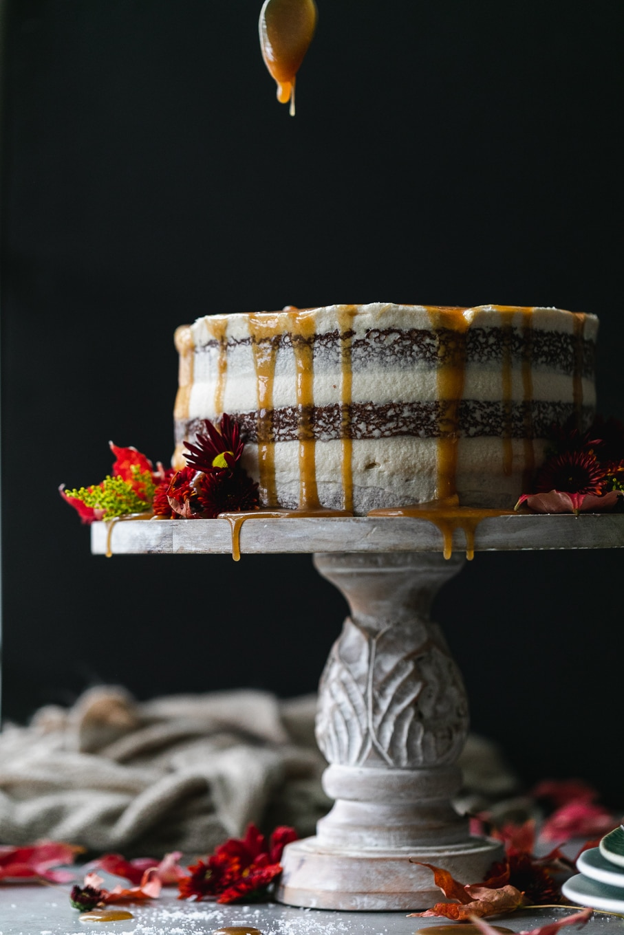 Straight on shot of a maple layer cake decorated with fall flowers