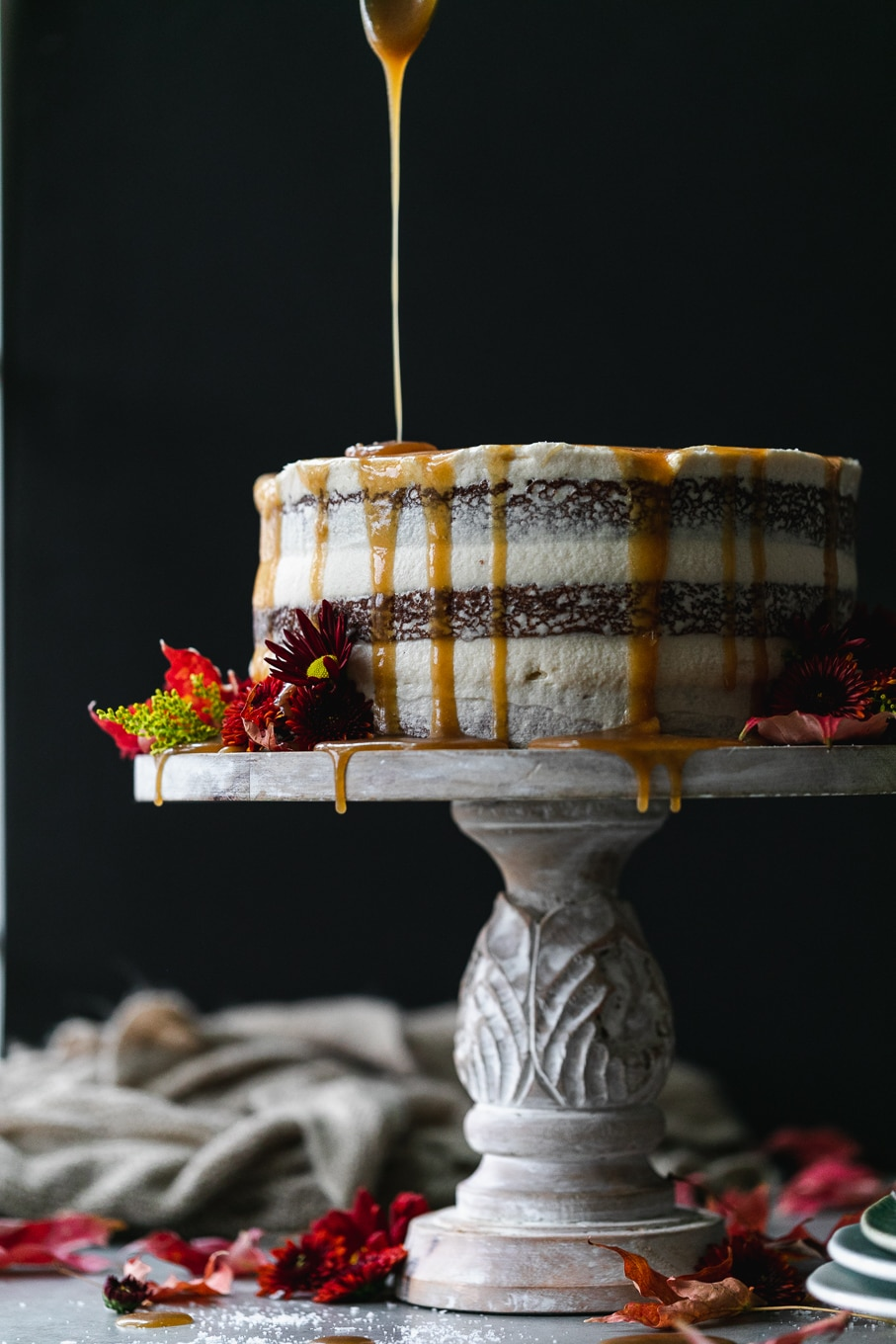 Straight on shot of a maple layer cake being drizzled with caramel