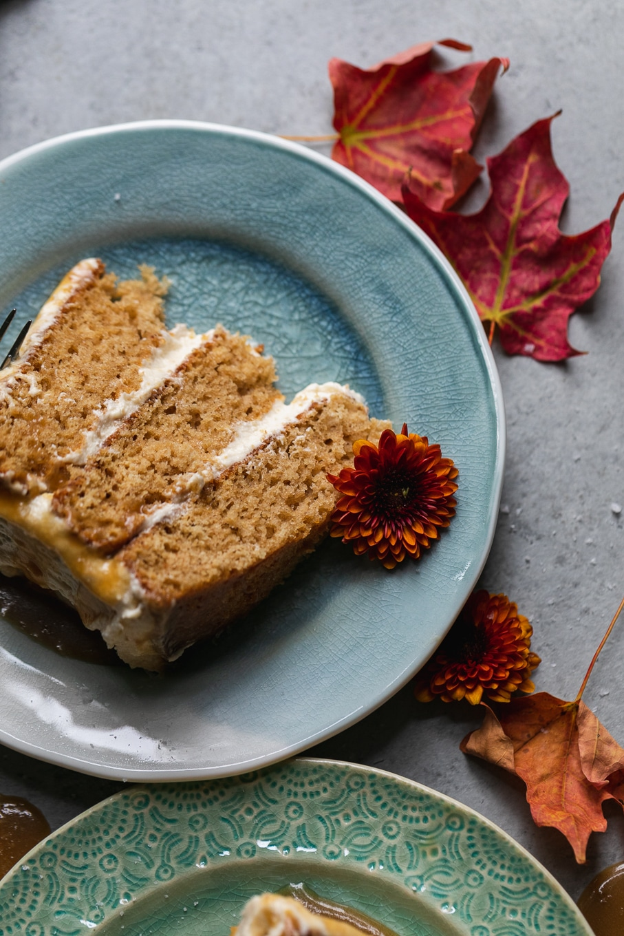 Close up shot of a slice of maple cake on a blue plate with an orange flower