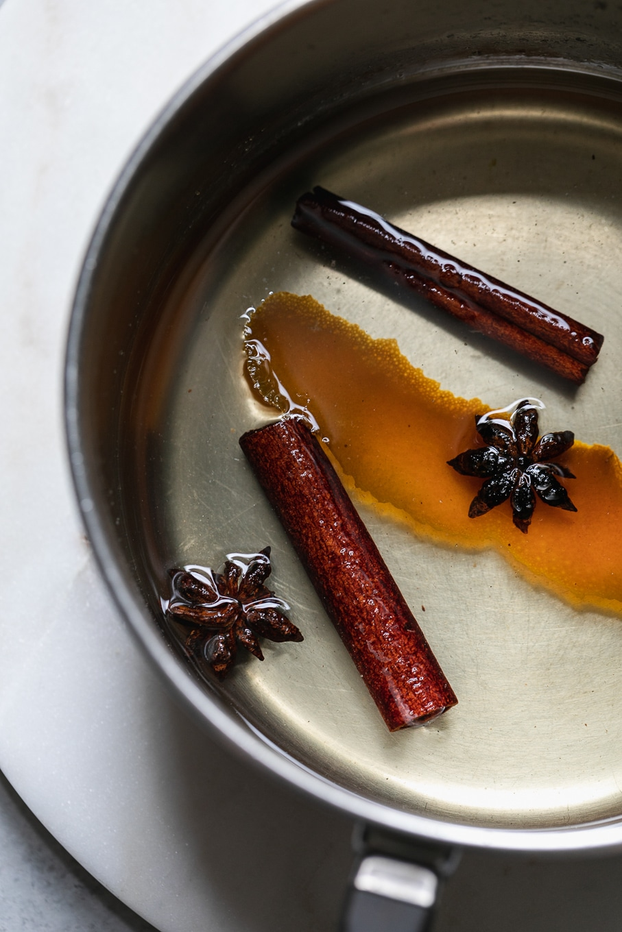 Close up shot of a saucepan filled with simple syrup, cinnamon sticks, star anise, and an orange peel