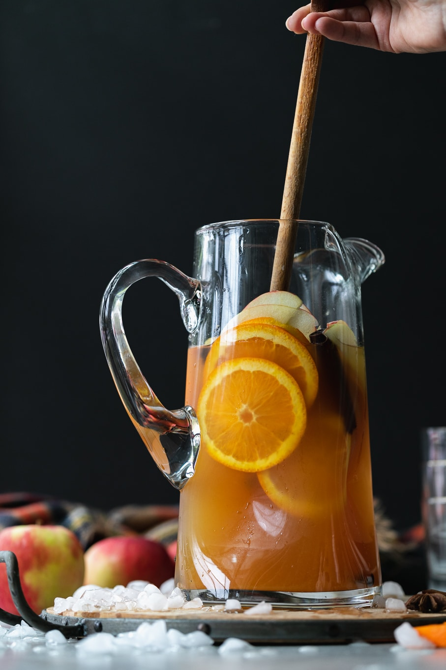 Straight on shot of a pitcher of apple cider sangria with orange slices