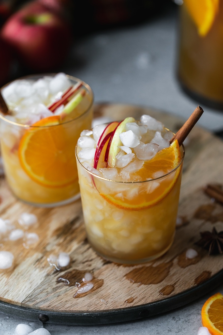 Close up shot of two glasses of apple cider sangria on a wooden circular tray