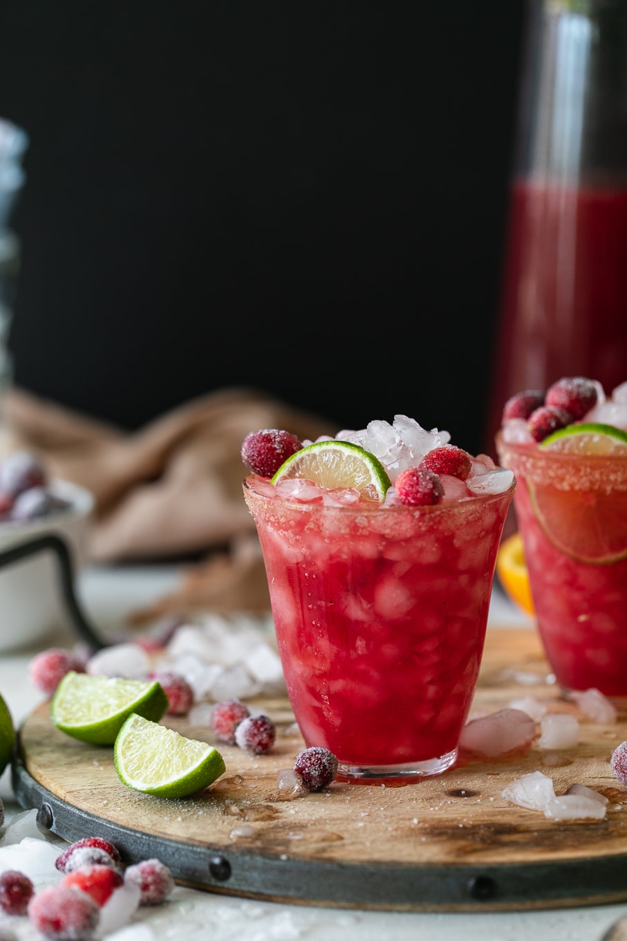 Shot of a cranberry margarita tarnished with lime and sugared cranberries