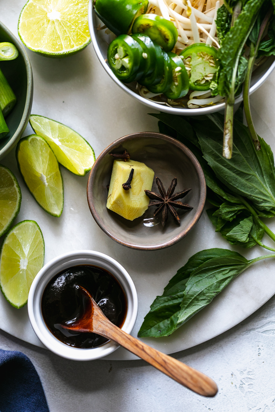 Overhead shot of lime wedges, ginger, sites, herbs, and hoisin sauce