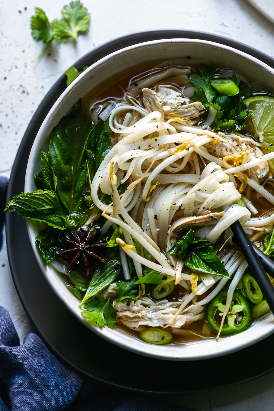 Overhead close up shot of a colorful bowl of pho with chopsticks in the bowl