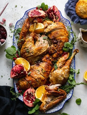 Overhead shot of a platter filled with turkey, herbs, pomegranate, and oranges