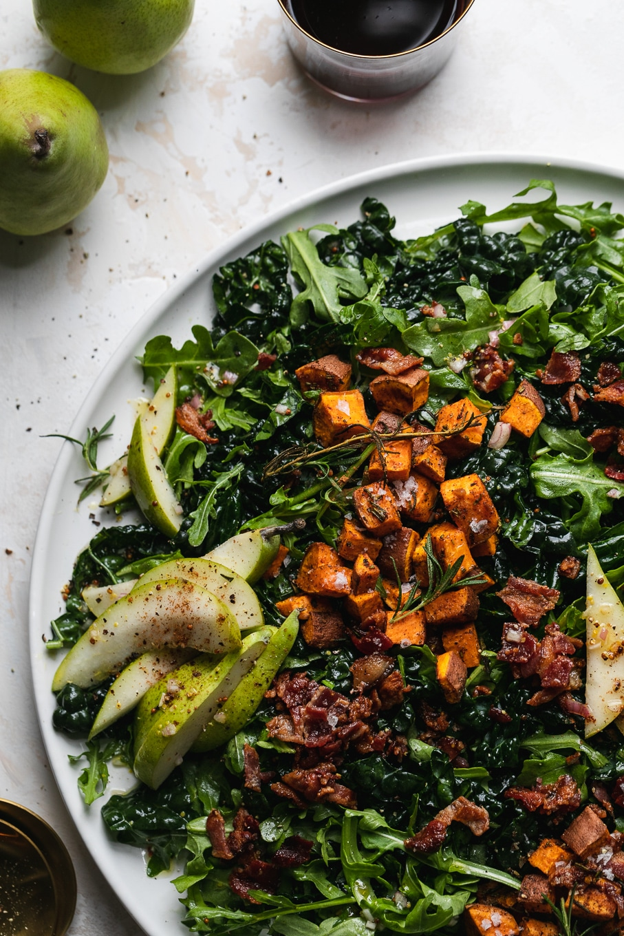 Overhead close up shot of kale salad with sweet potato, pear, and bacon