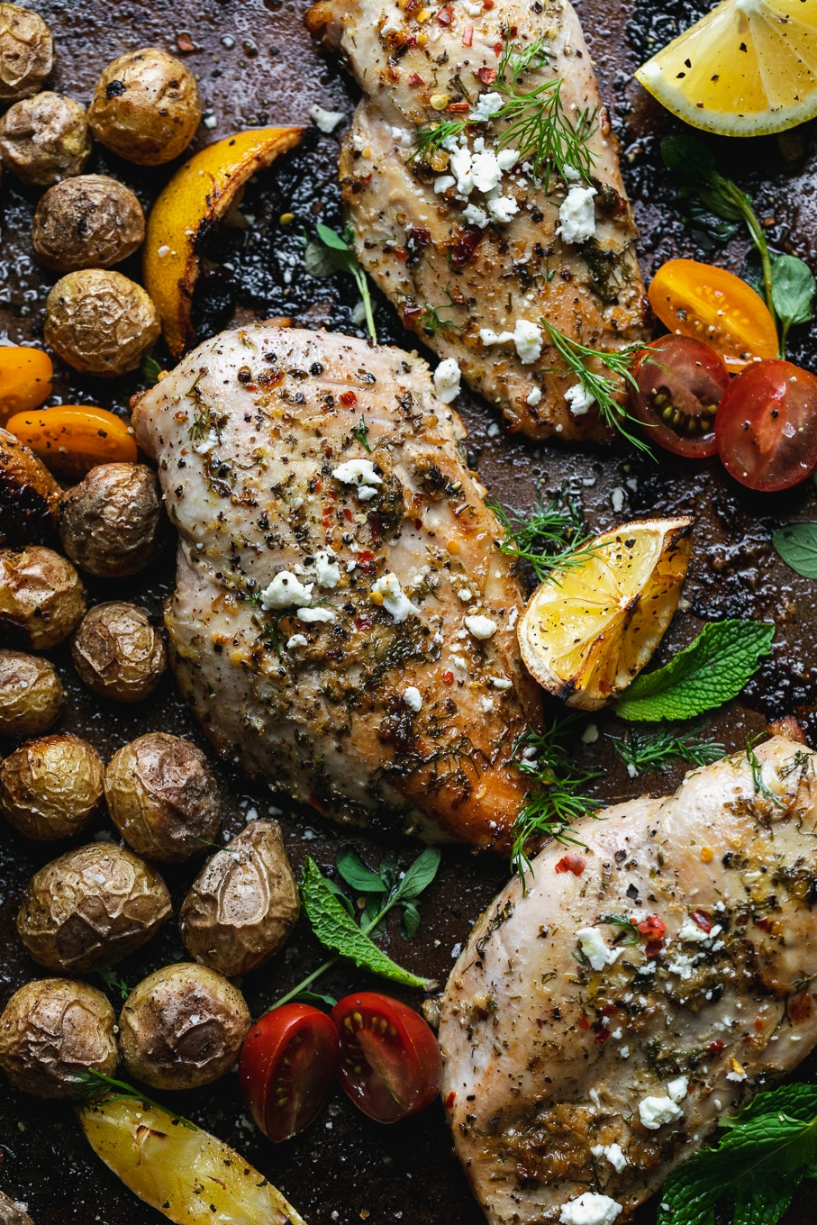 Close up shot of chicken and baby potatoes on a sheet pan