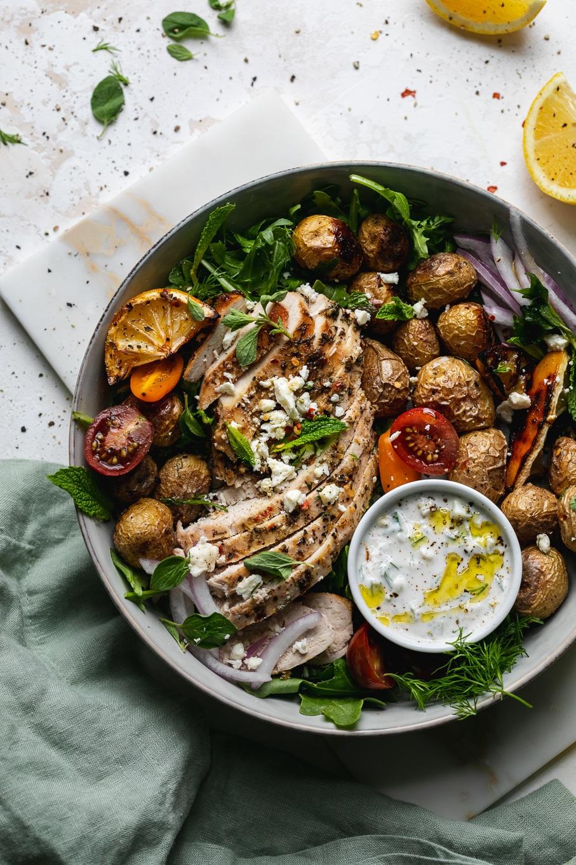 Overhead shot of a bowl of chicken, potatoes, tomatoes, lemon, arugula, herbs, and tzatziki sauce