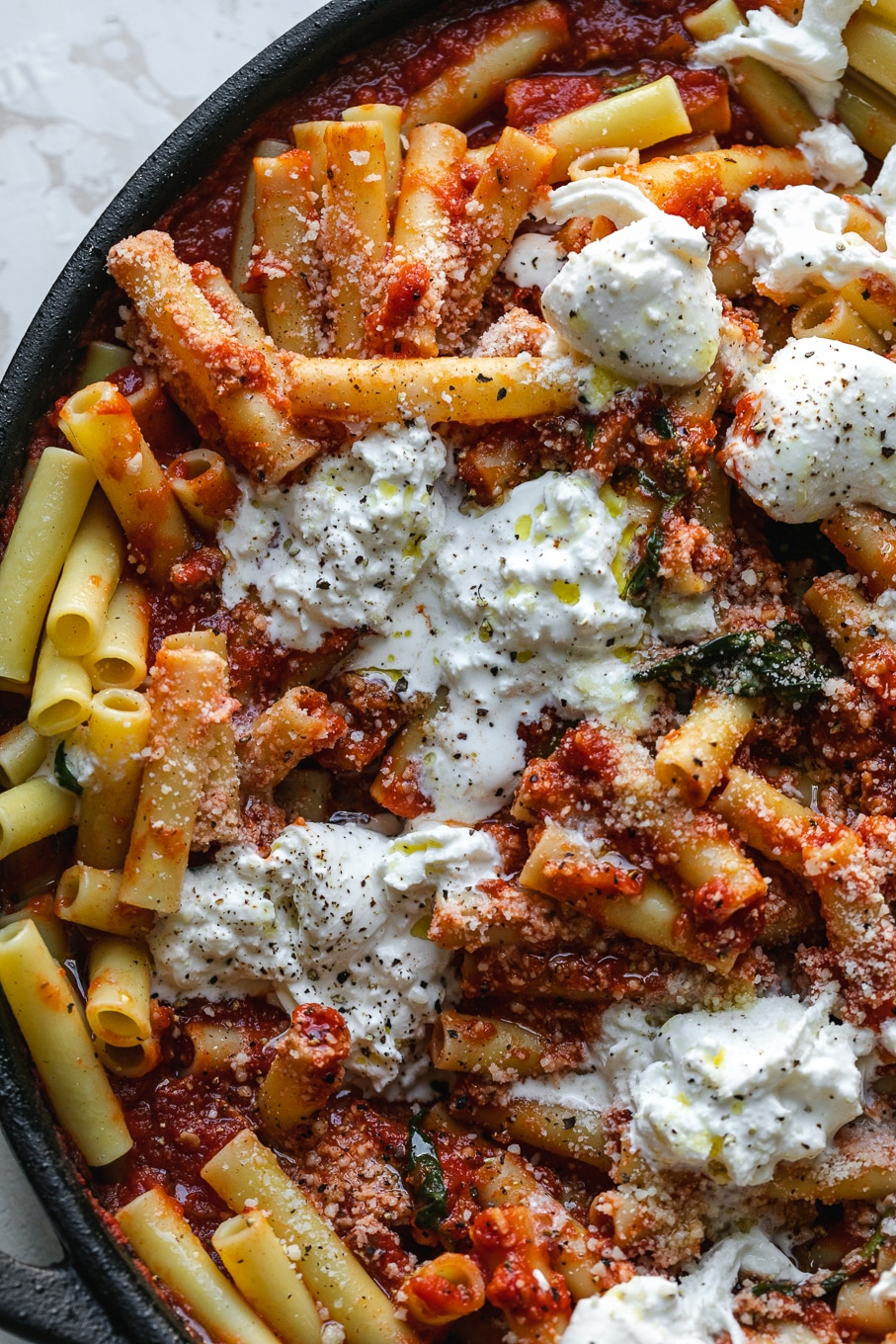 Overhead close up shot of pasta being tossed with tomato sauce and burrata
