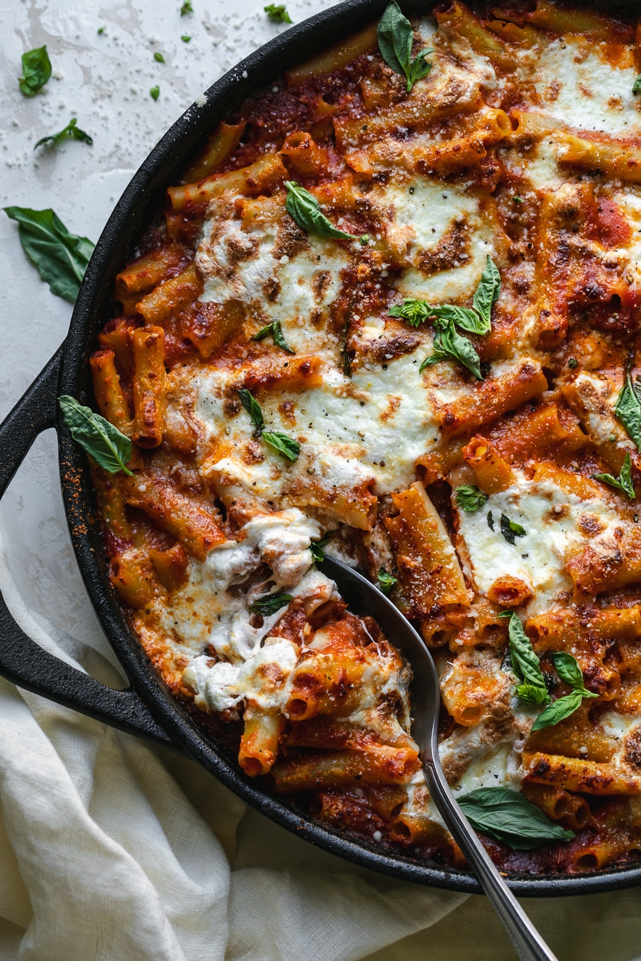 Overhead shot of a skillet of baked ziti with a spoon digging in