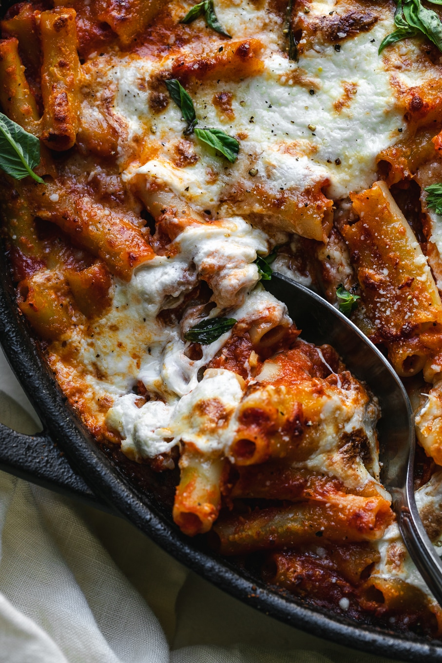 Close up shot of a skillet of baked pasta with a spoon digging in