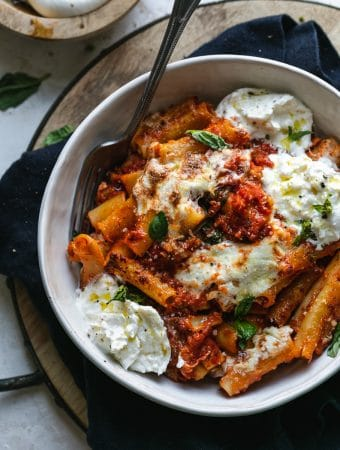Overhead close up shot of a bowl of burrata baked ziti with a fork in the bowl