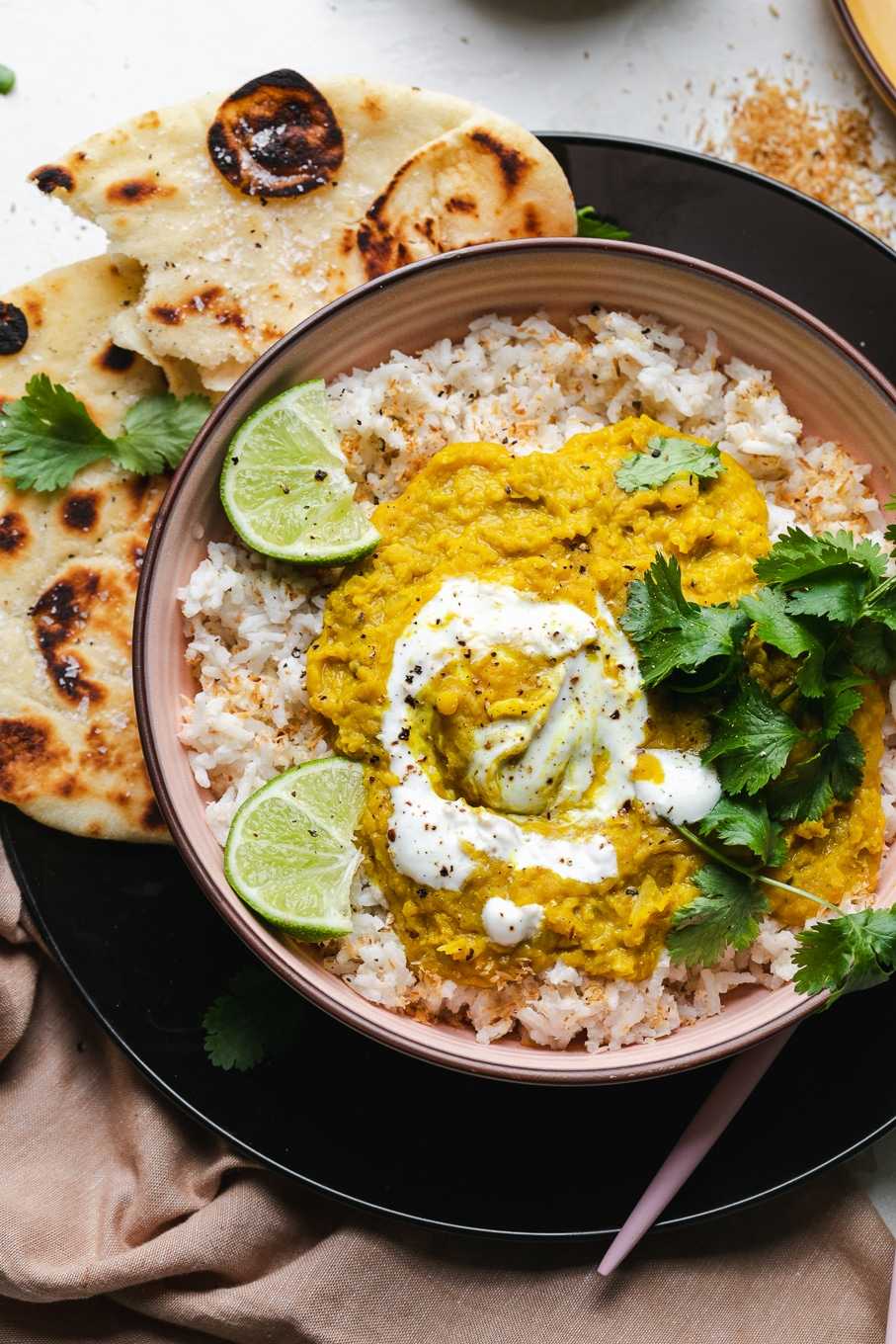 Overhead shot of a bowl with rice, lentil dal, cilantro, and lime wedges
