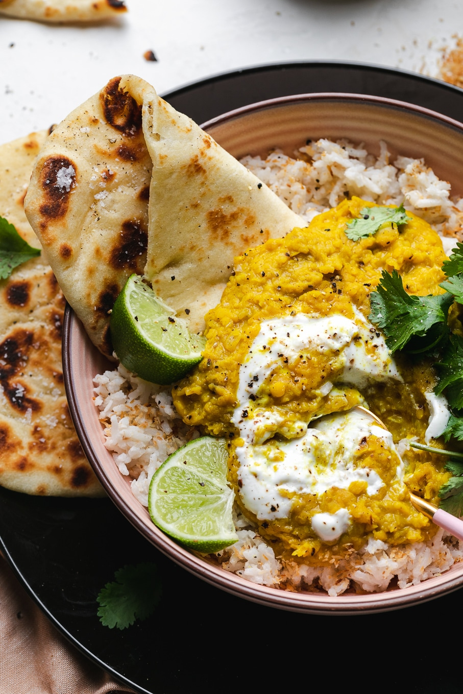 Overhead close up shot of a bowl of toasted coconut rice, dal, lime wedges, cilantro, and naan