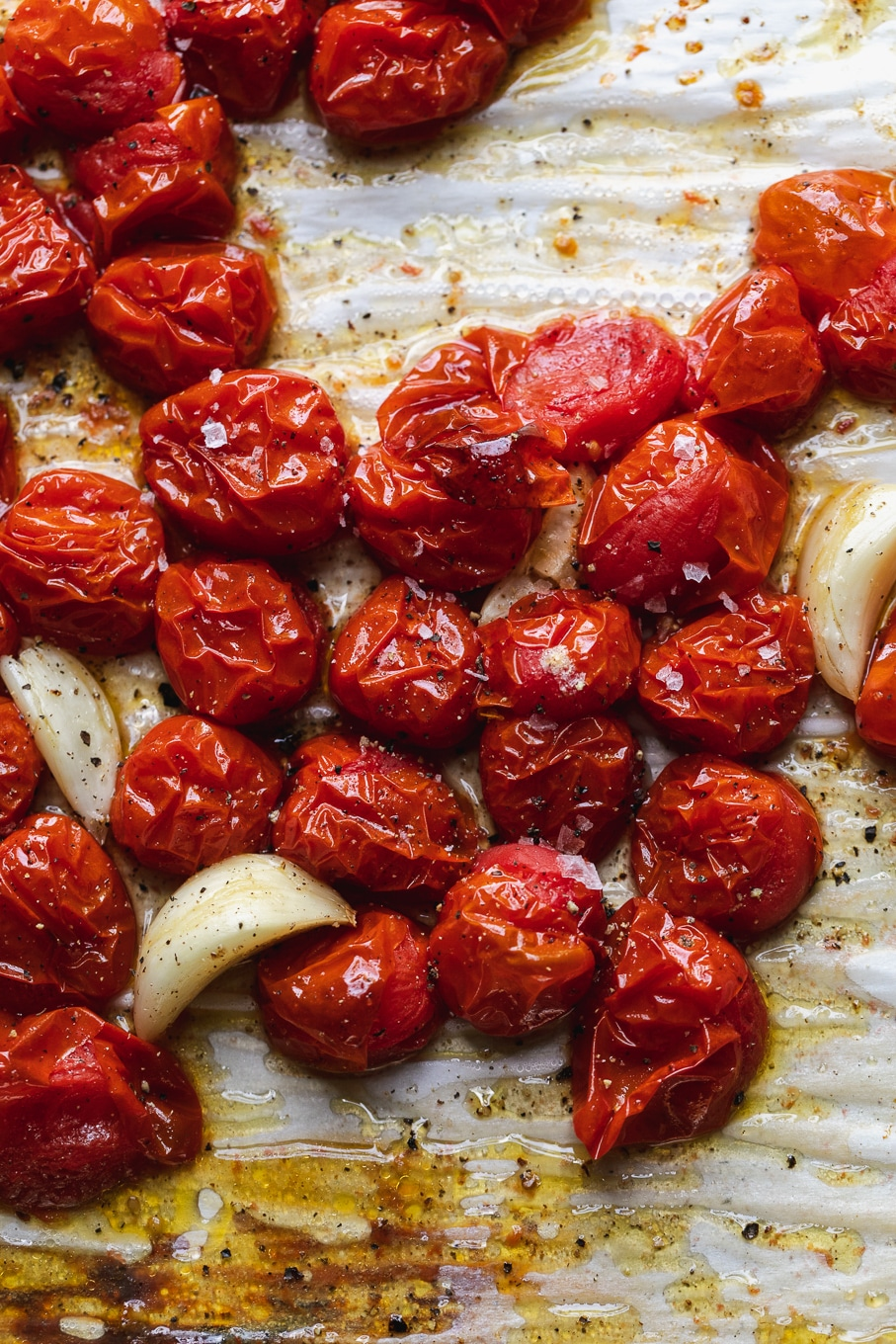 Overhead close up shot of roasted tomatoes and garlic cloves