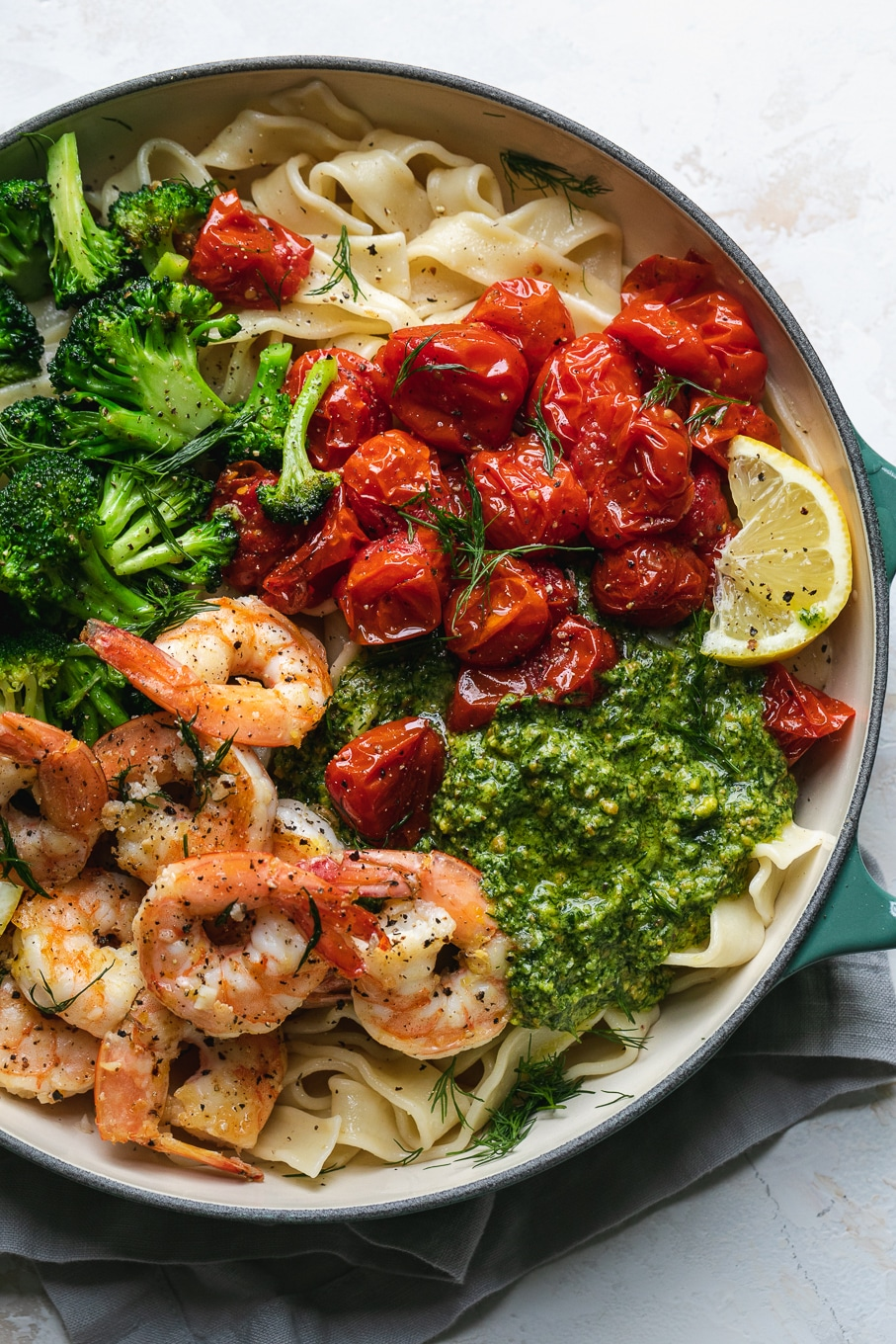 Overhead shot of a pan filled with piles of veggies, shrimp and pesto over pasta