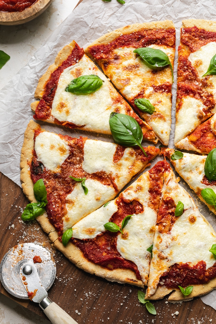 Overhead shot of a pizza cut into slices with fresh basil