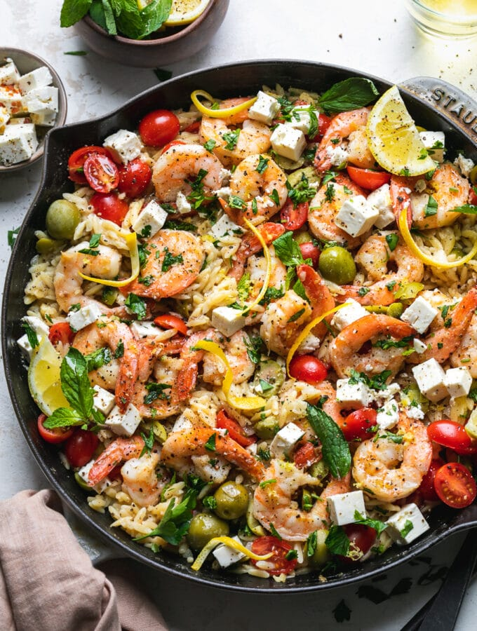 Overhead shot of a pan of orzo with shrimp, tomatoes, herbs, feta, and lemon
