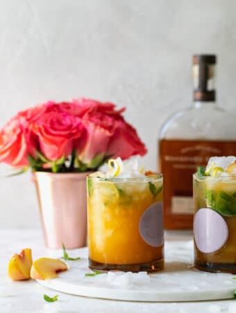 Straight on shot of peach basil cocktails with roses in the background